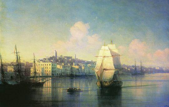 Вид приморского города вечером с зажженным маяком