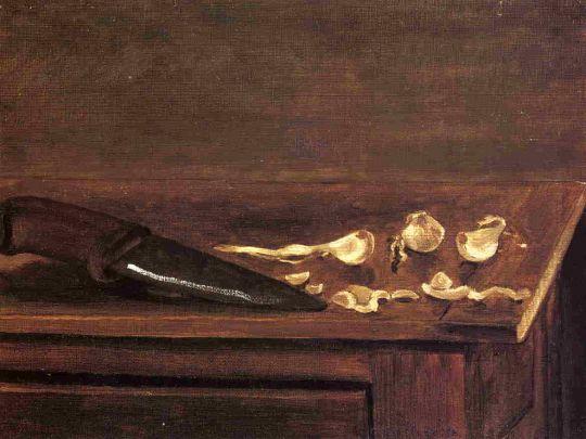 Зубчик чеснока и нож на углу стола